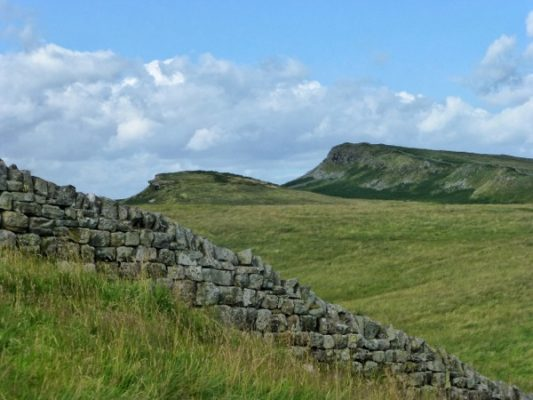 Le mur d'Hadrien au premier plan et à l'arrière-plan, sur la colline de droite