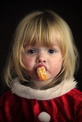 Une fillette mange un quartier d'orange pour Noël