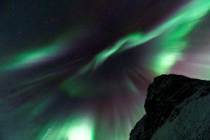 """Une aurore boréale """"couronne"""" surplombe un sommet enneigé"""