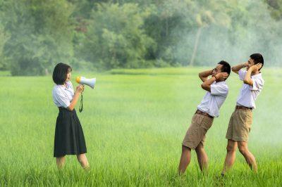 Une personne parle dans un microphone, deux autres se couvrent les oreilles de leurs mains, dérangées par le bruit