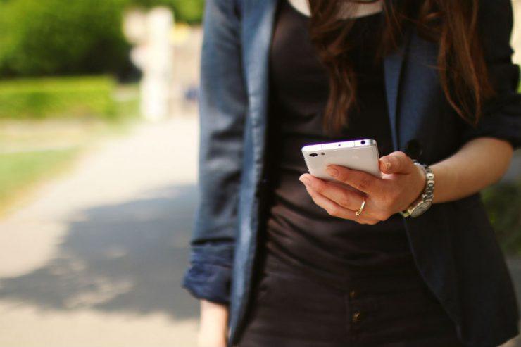 Une jeune femme, peut-être de la génération Z, tient un smartphone dans sa main
