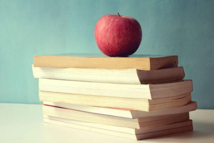 Une pile de livres avec un pomme rouge au-dessus
