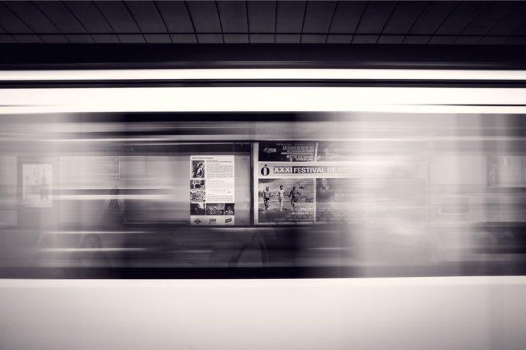 Un métro passe, permettant d'entrevoir les publicités en arrière-plan
